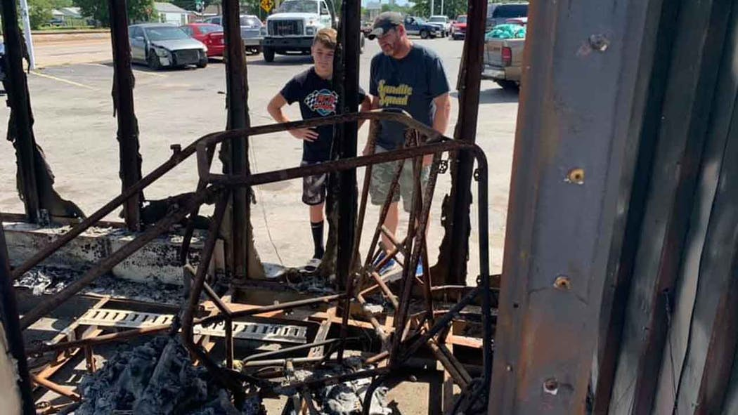 Hayden and his father inspect their burned out trailer.