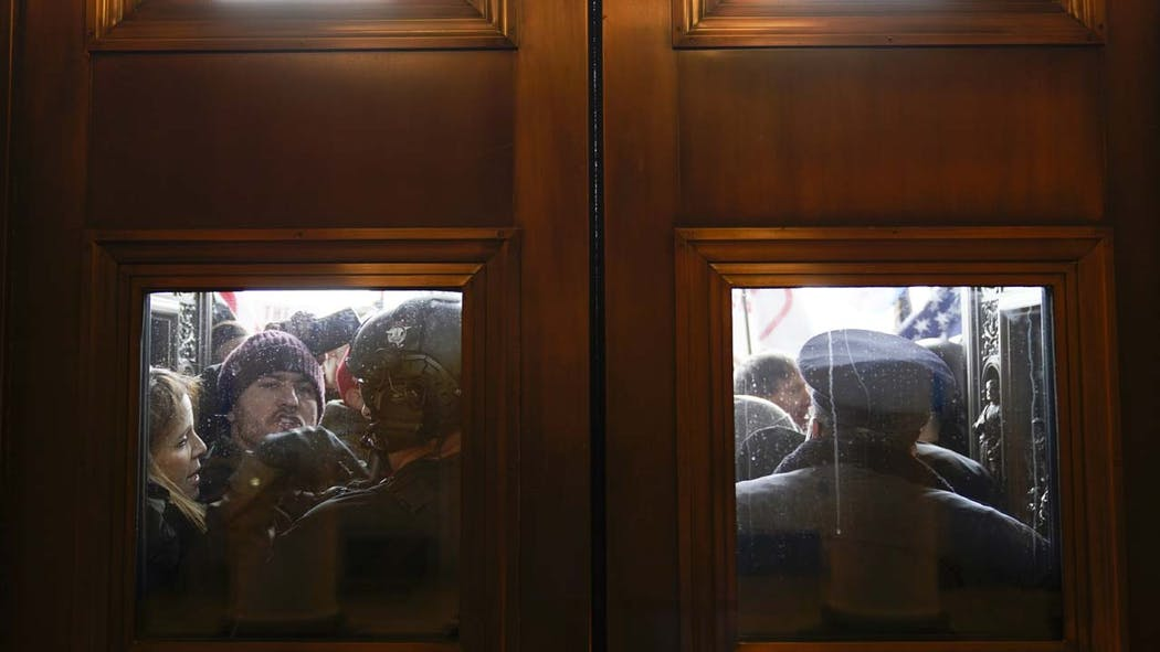Photo of protestors outside the Capitol doors.